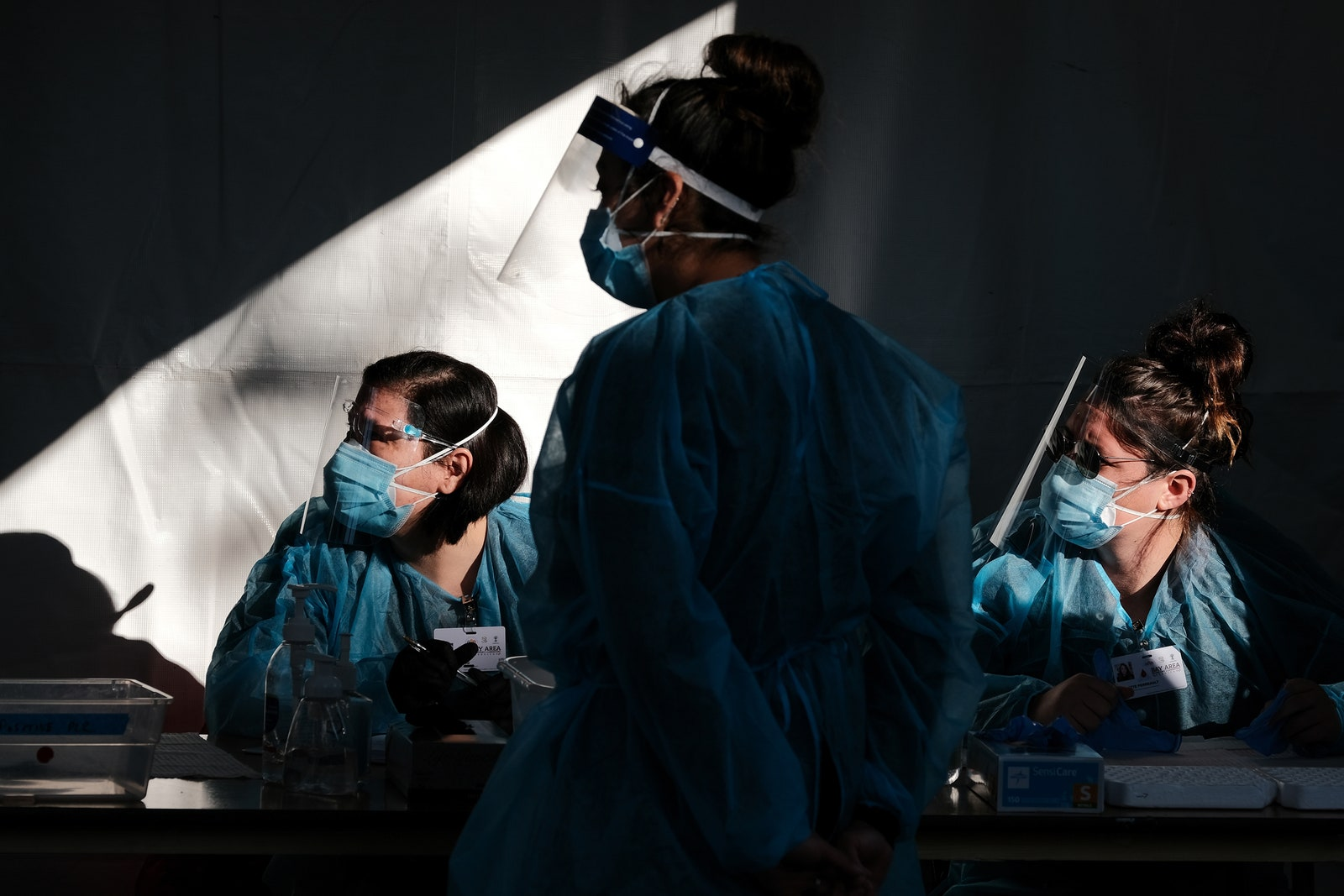 Three healthcare workers in PPE.