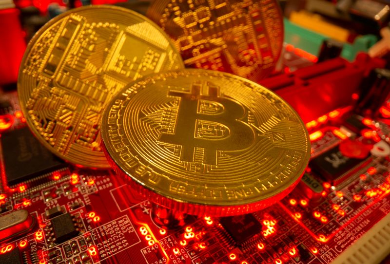 Representations of the virtual currency Bitcoin stand on a motherboard in this picture illustration