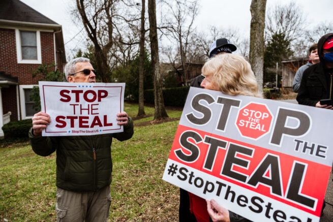LOUISVILLE, KY - JANUARY 02: DC Under Siege protesters display their Stop The Steal signs in front Sen. Majority Leader Mitch McConnell's vandalized home on January 2, 2021 in Louisville, Kentucky. Black Lives Matter demonstrators and right-wing DC Under Siege members gathered during the Won't Back Down Rally to protest Sen. McConnell's decision to block the most recent stimulus bill. (Photo by Jon Cherry/Getty Images)