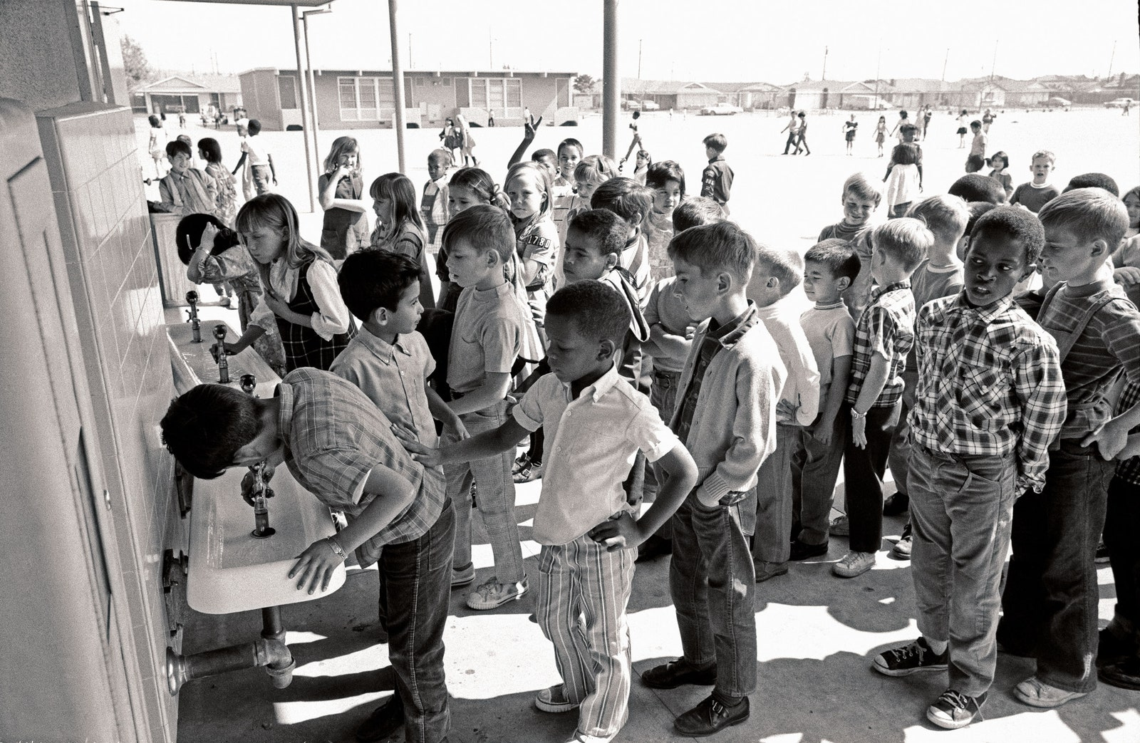 Children at a desegregated school in California in 1970 line up at drinking fountains
