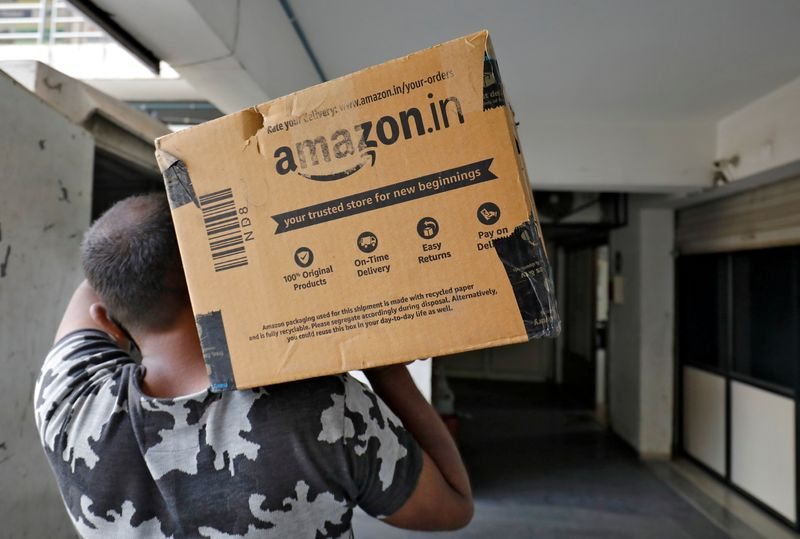FILE PHOTO: A delivery worker carries an Amazon package in Ahmedabad