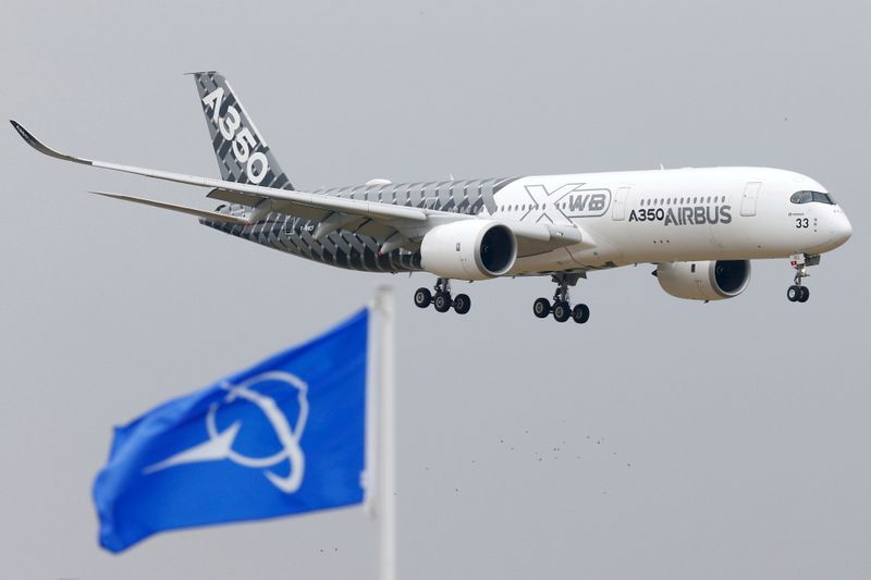FILE PHOTO: An Airbus A350 jetliner flies over Boeing flags as it lands after a flying display during the 51st Paris Air Show at Le Bourget airport near Paris