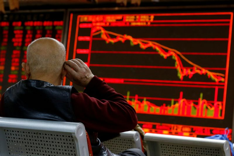 FILE PHOTO: An investor sits in front of a board showing stock information at a brokerage office