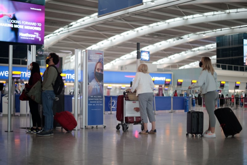 Passengers walk at the Terminal 5 departures area at Heathrow Airport in London