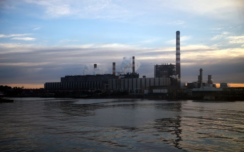Smoke comes out of an electric plant on the shore of the polluted River Plate in Buenos Aires
