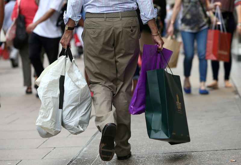 FILE PHOTO: Shoppers carry bags in London