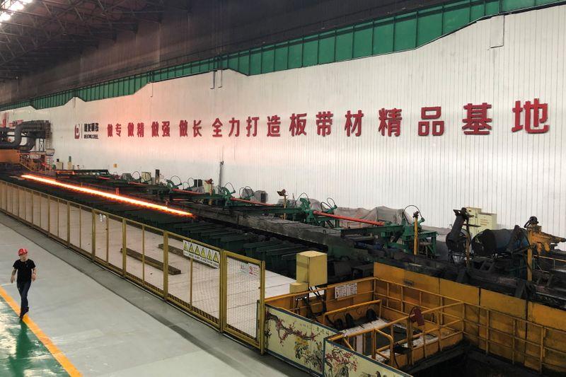 FILE PHOTO: Man walks inside a steel plant of Delong Steel in Xingtai