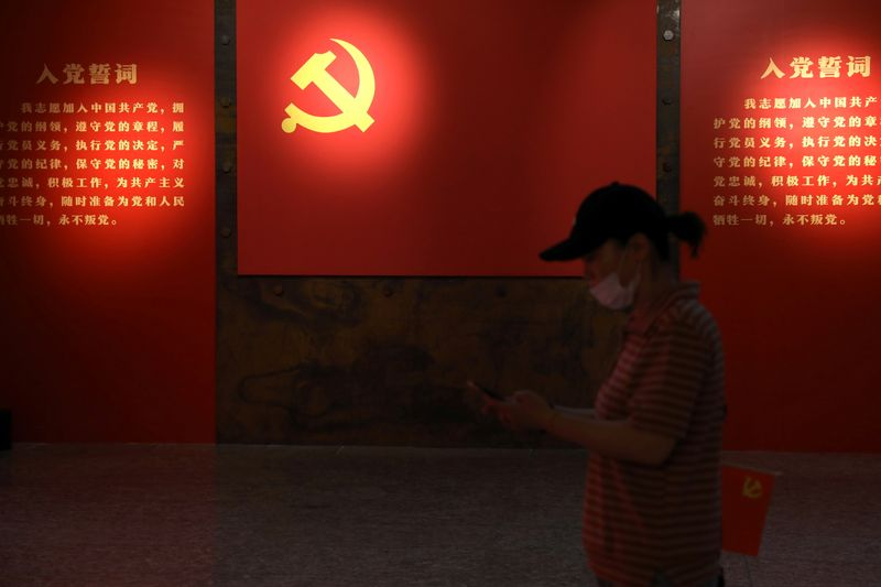 A visitor walks past a board with an emblem of the Communist Party of China at an exhibition marking the 100th anniversary of the founding of the Party, in Beijing