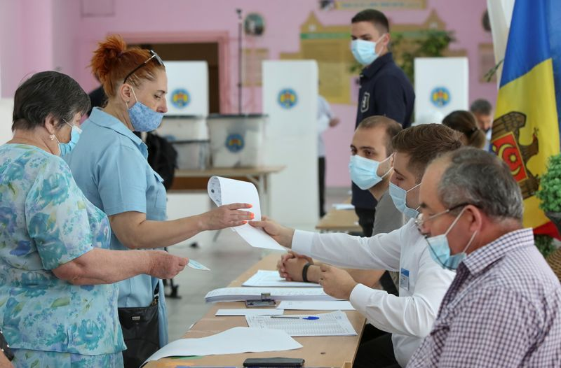 People queue to receive ballots during a vote at a snap parliamentary election, in Chisinau