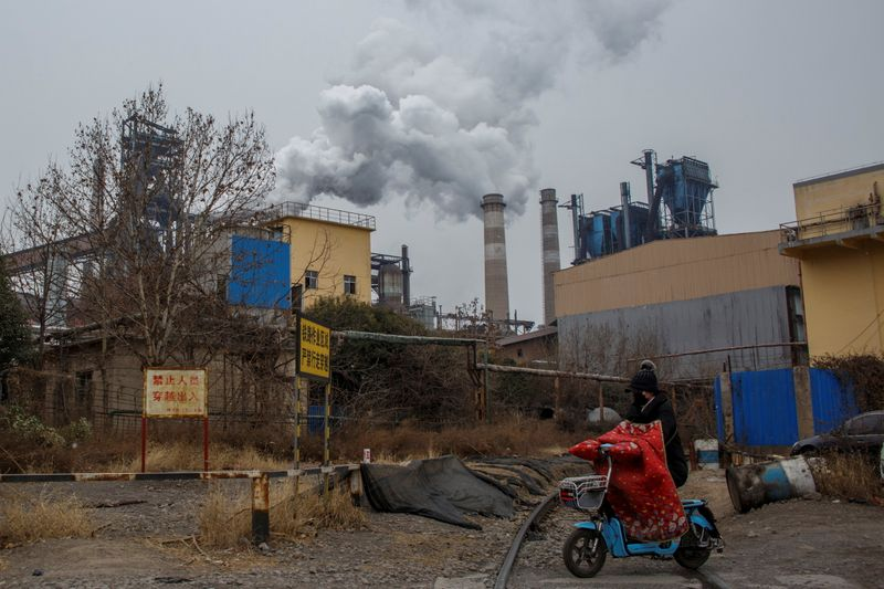 FILE PHOTO: A woman rides a scooter past a steel plant in Anyang
