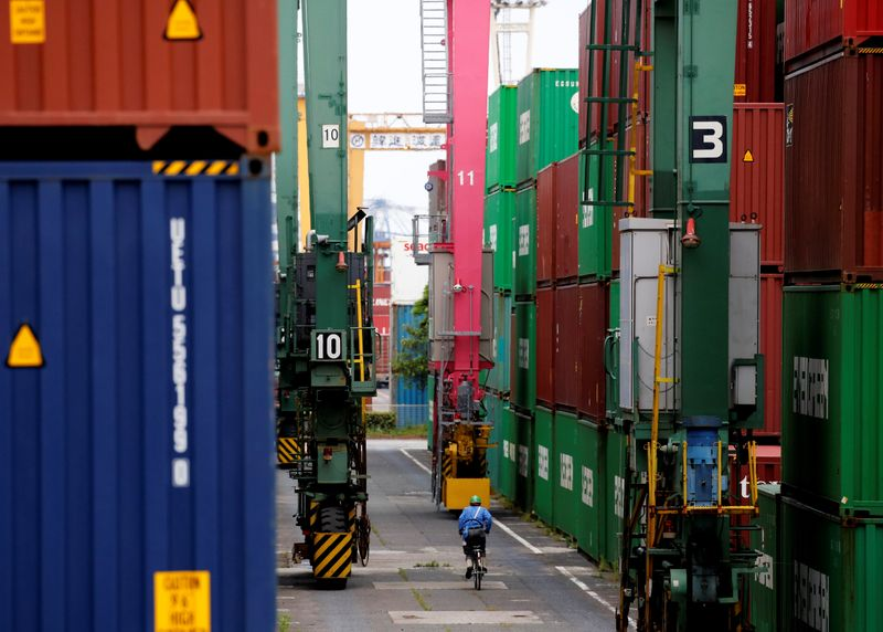 A man in a bicycle drives past containers at an industrial port in Tokyo