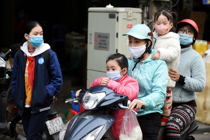 FILE PHOTO: A family wears protective masks as they ride a motorbike in the street in Hanoi