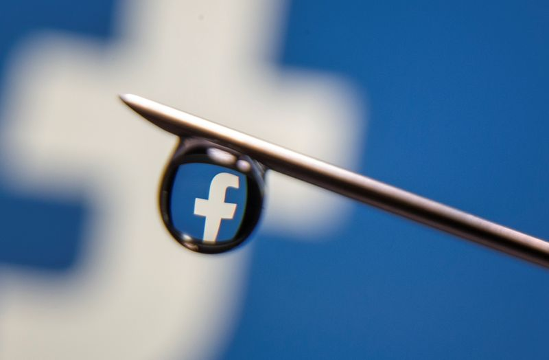 FILE PHOTO: Facebook logo is reflected in a drop on a syringe needle in this illustration photo