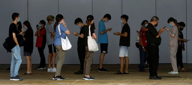 FILE PHOTO: People who had visited a mall which became a coronavirus disease (COVID-19) cluster, queue up for their swab tests in Singapore