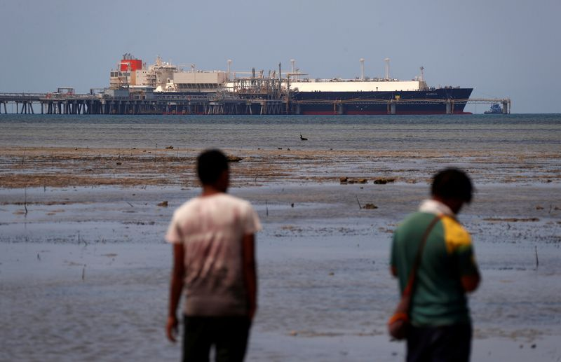 FILE PHOTO: Locals walk along small beach where LNG carrier called Kumul is docked at marine facility of ExxonMobil PNG Limited operated LNG plant at Caution Bay, located on outskirts of Port Moresby