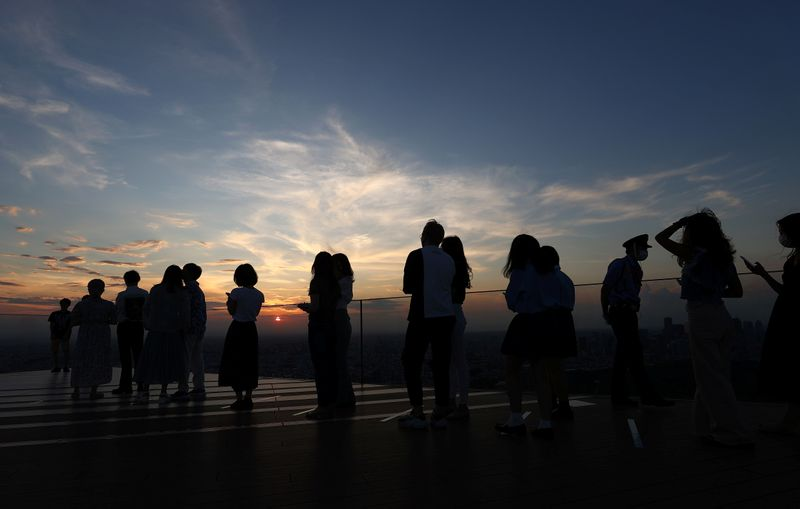People queue up to get their picture taken in front of the sunset on top of Shibuya Sky observation deck, in Tokyo