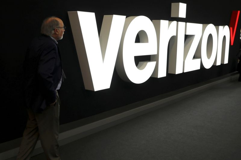 A man stands next to the logo of Verizon at the Mobile World Congress in Barcelona