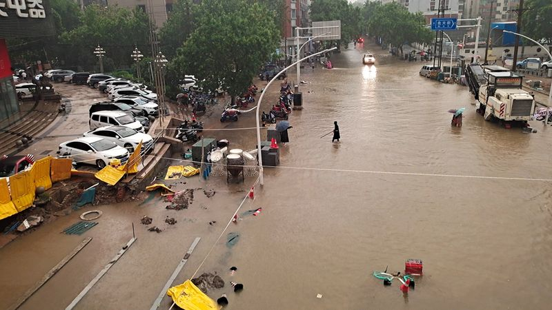 People wade through floodwaters on a road amid heavy rainfall in Zhengzhou