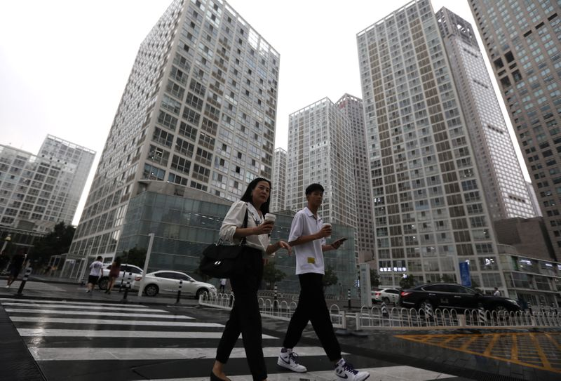 FILE PHOTO: People walk past an office compound in Beijing's Central Business District (CBD),