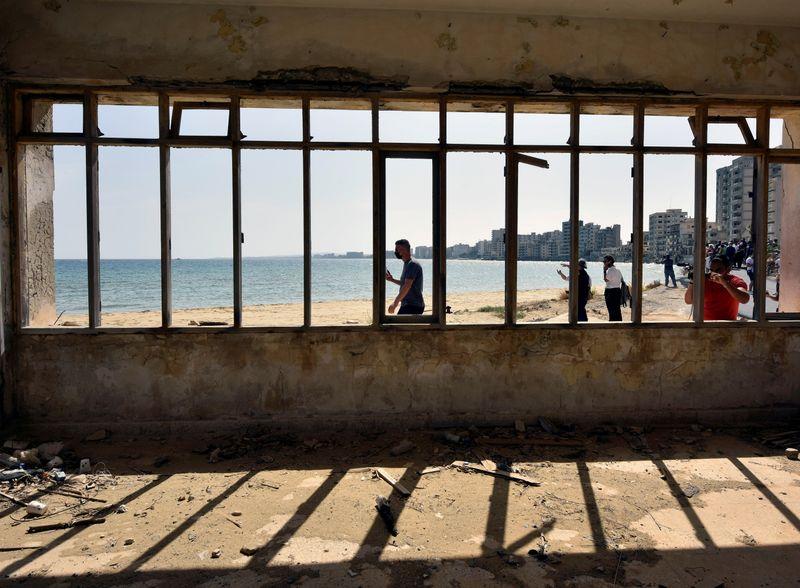 FILE PHOTO: People walk on a beach in the abandoned coastal area of Varosha