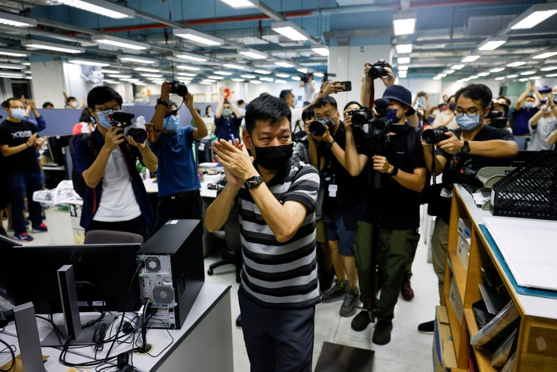 FILE PHOTO: FILE PHOTO: Staff members of Apple Daily work on their final edition in Hong Kong