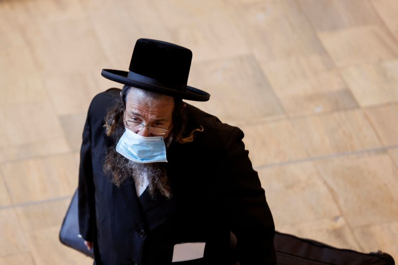 FILE PHOTO: An ultra-Orthodox Jewish man wearing a face mask, carries his luggage at the arrivals terminal in Israel's Ben Gurion International Airport, amid a spread of the Delta variant of the coronavirus disease (COVID-19), near Tel Aviv