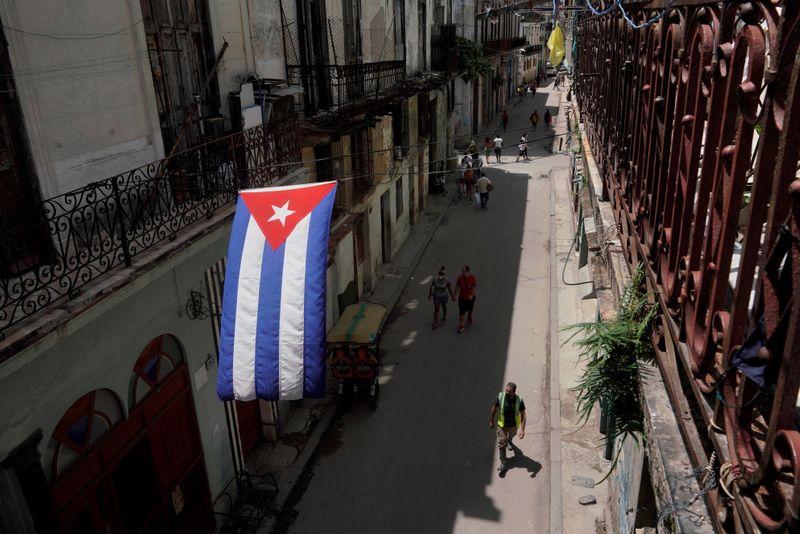 A Cuban flag hangs over a street in Havana