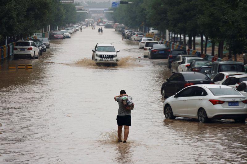 Man wades through a flooded road following heavy rainfall in Zhengzhou