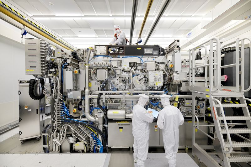 FILE PHOTO: Employees are seen working on the final assembly of ASML's TWINSCAN NXE:3400B semiconductor lithography tool with its panels removed, in Veldhoven