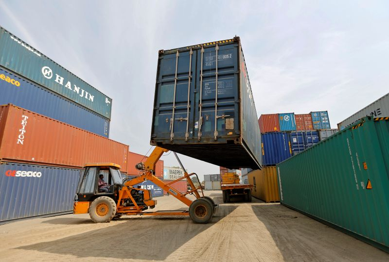 FILE PHOTO: A mobile crane carries a container at Thar Dry Port in Sanand in the western state of Gujarat, India