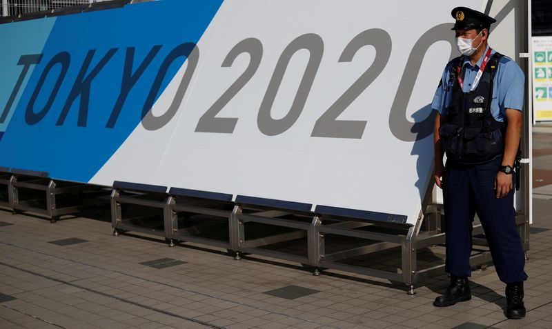 A police officer wearing a face mask stands near the entrance of the Main Press Centre, ahead of the Tokyo 2020 Olympic Games, in Tokyo