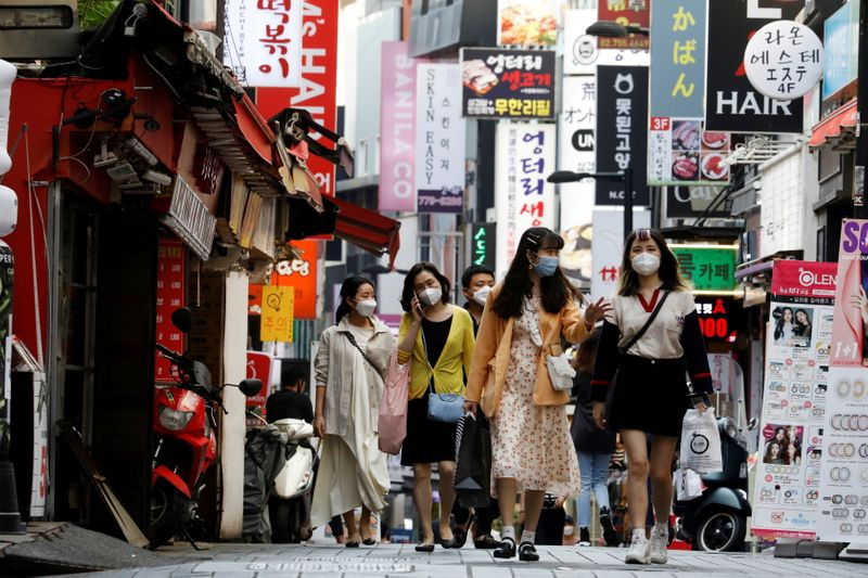 FILE PHOTO: People wearing masks walk at Myeongdong shopping district amid social distancing measures to avoid the spread of the coronavirus disease (COVID-19), in Seoul