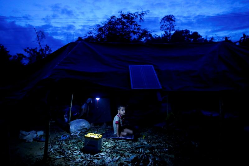 FILE PHOTO: A Rohingya refugee boy sits inside his temporary shelter near Balukhali in Cox's Bazar
