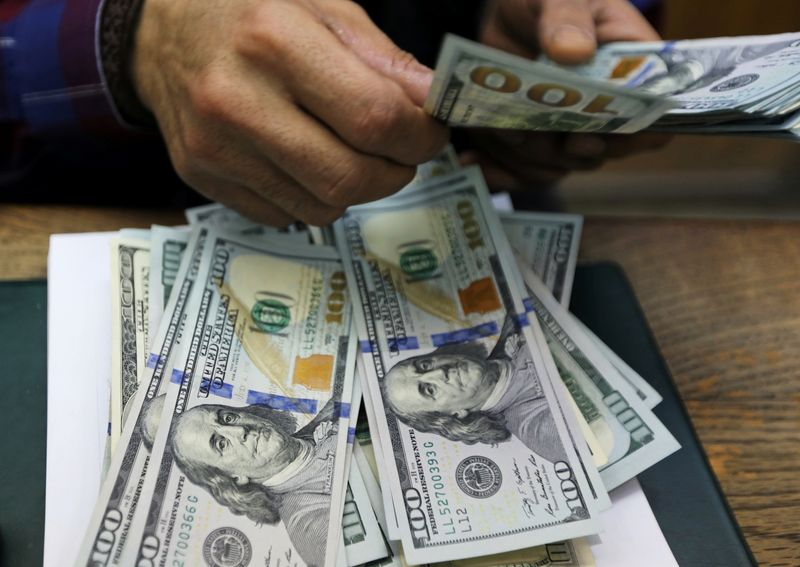 An employee counts U.S dollar bills at a money exchange office in central Cairo