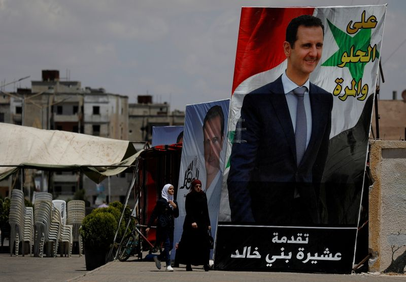 FILE PHOTO: People walk past posters depciting Syria's President Bashar al-Assad, in the district of al-Waer