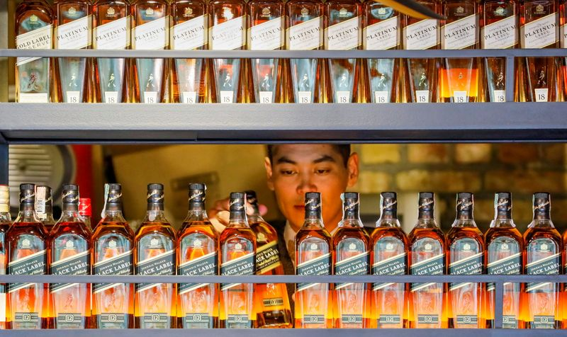 FILE PHOTO: A bartender takes a bottle of Johnnie Walker whisky at Barmaglot bar in Almaty