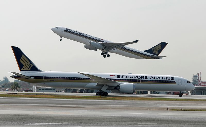 FILE PHOTO: A Singapore Airlines Airbus A330 plane takes off behind a Boeing 787 Dreamliner at Changi Airport in Singapore