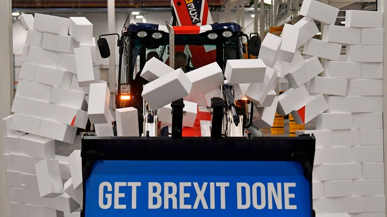"""Britain's Prime Minister and Conservative party leader Boris Johnson drives a Union flag-themed JCB, with the words """"Get Brexit Done"""" inside the digger bucket, through a fake wall emblazoned with the word """"GRIDLOCK"""", during a general election campaign event at JCB construction company in Uttoxeter, Staffordshire, on December 10, 2019. - Britain will go to the polls on December 12, 2019 to vote in a pre-Christmas general election. (Photo by Ben STANSALL / POOL / AFP)"""